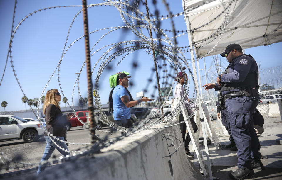 An Immigration and Customs Enforcement (ICE) agents check pedestrians' documentation at the San Ysidro Port of Entry on October 2, 2019 in San Ysidro, California. - Fentanyl, a powerful painkiller approved by the US Food and Drug Administration for a range of conditions, has been central to the American opioid crisis which began in the late 1990s. China was the first country to manufacture illegal fentanyl for the US market, but the problem surged when trafficking through Mexico began around 2005, according to Donovan. (Photo by SANDY HUFFAKER / AFP) (Photo by SANDY HUFFAKER/AFP via Getty Images)