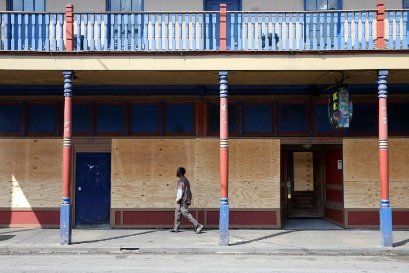 A man walks past a boarded up business on Frenchmen Street in New Orleans