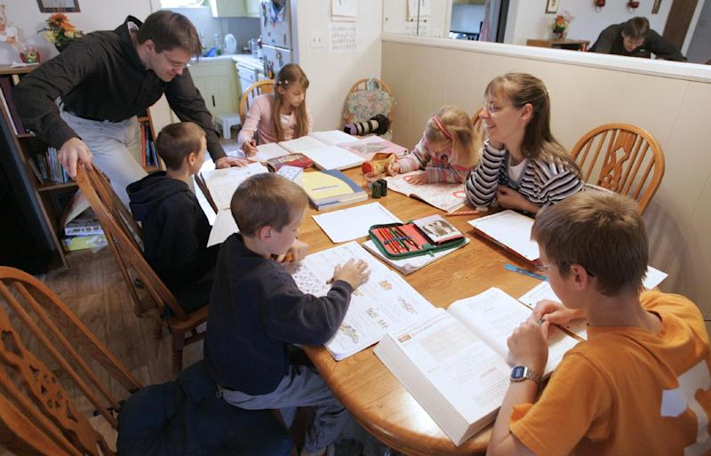 FILE -- This March 13, 2009, file photo shows Uwe Romeike, top left, and his wife Hannelore, second from right, teaching their children at their home in Morristown, Tenn. The couple fled Germany with their five children over fears that they would lose custody for not sending the children to school, and are now asking a federal appeals court to grant them asylum in the U.S. (AP Photo/Wade Payne, File)