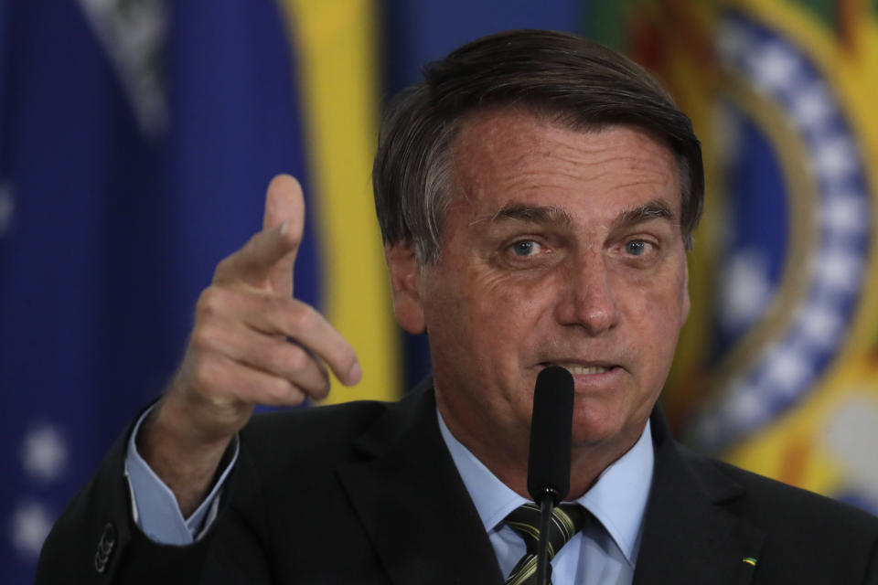 "Brazilian President Jair Bolsonaro points to the press as he refers to his recovery from COVID-19 and his past as an athlete, during a ceremony coined ""Brazil winning COVID-19"" at Planalto presidential palace in Brasilia, Brazil, Monday, Aug. 24, 2020. (AP Photo/Eraldo Peres)"