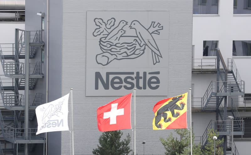 FILE PHOTO: Swiss national flag flies beside a flag of the canton of Bern in front of the logo of Nestle in Konolfingen