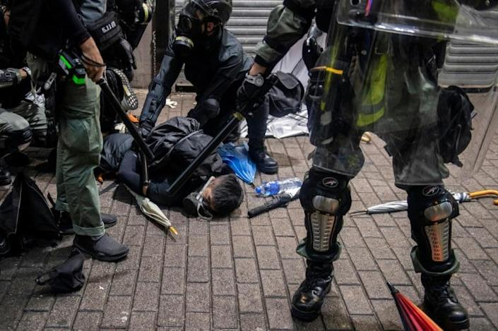 A protester (C) is detained by police during clashes in the Wan Chai district in Hong Kong (AFP Photo/NICOLAS ASFOURI)
