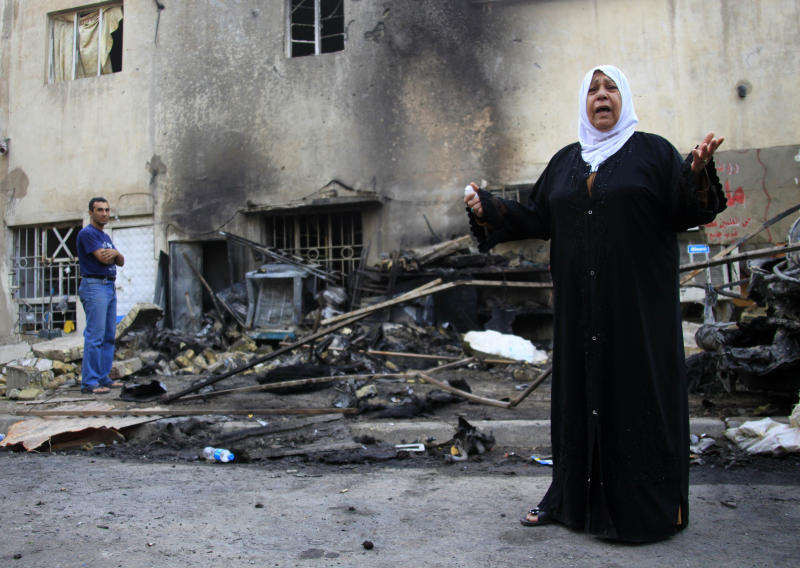 A woman grieves for her sister, who died in a bombing Friday, while inspecting the site of the car bomb attack in Baghdad, Iraq, Saturday, Oct. 19, 2013. Police officials said the Friday night blast took place in the capital's eastern Mashtal neighborhood. Violence in Iraq has escalated sharply since April, 2013, following a deadly crackdown by security forces on a camp for Sunni protesters in the northern town of Hawija. (AP Photo/Hadi Mizban)