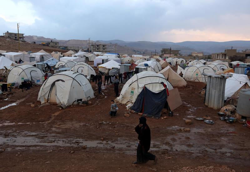 A Syrian refugee woman walks near the tents of a refugee camp in the eastern Lebanese border town of Arsal, Monday, Nov. 18, 2013. Thousands of Syrians have fled to Lebanon over the past days as government forces attack the western town of Qarah near the border with Lebanon. (AP Photo/Bilal Hussein)
