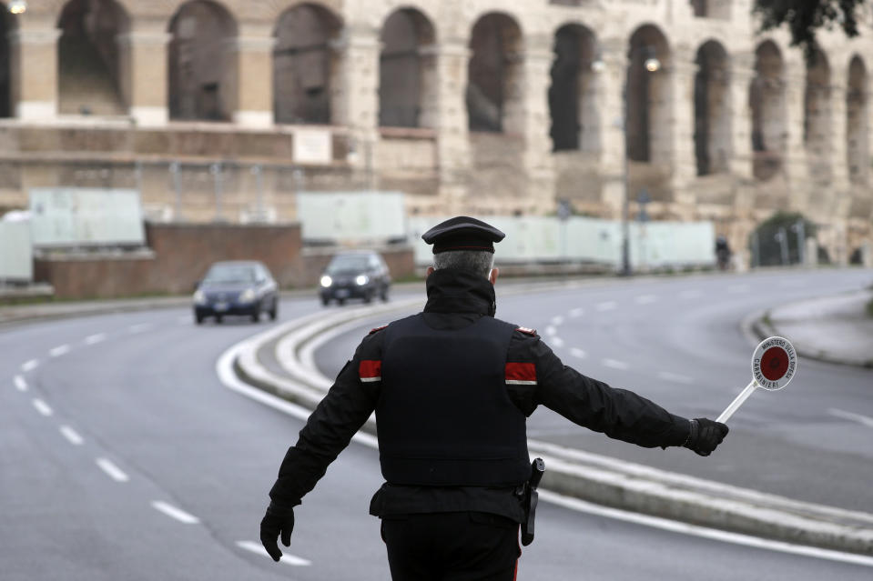 Italian Carabinieri officers check vehicles near the Colosseum in Rome, Thursday, Dec. 24, 2020. Italians are easing into a holiday season full of restrictions, and already are barred from traveling to other regions except for valid reasons like work or health. Starting Christmas eve, travel beyond city or town borders also will be blocked, with some allowance for very limited personal visits in the same region. (AP Photo/Gregorio Borgia)