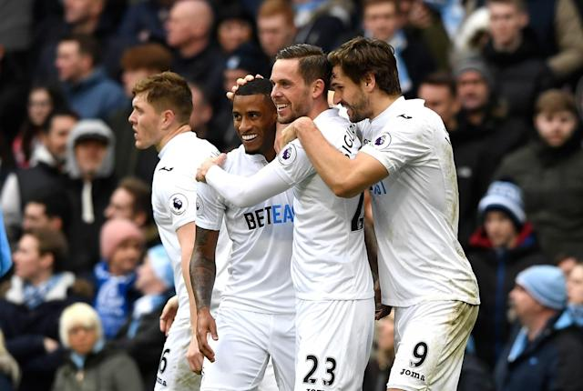 <p>Gylfi Sigurdsson of Swansea City celebrates scoring his sides first goal with team mates during the Premier League match between Manchester City and Swansea City at Etihad Stadium on February 5, 2017 in Manchester, England. </p>