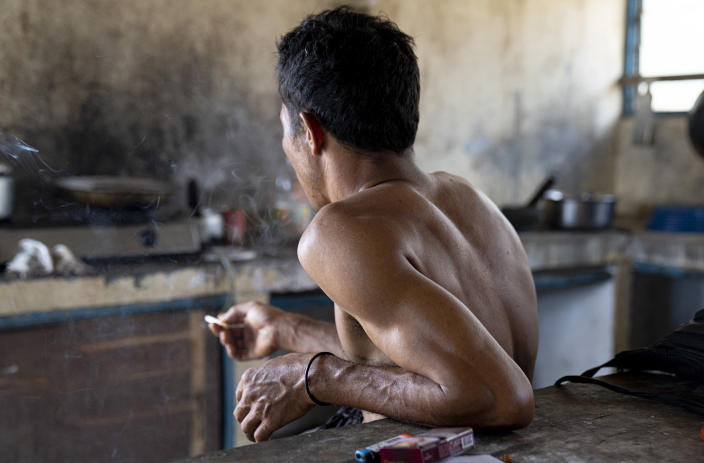 An Indonesian migrant worker rests after working on a palm oil plantation run by the government-owned Felda in Malaysia, in early 2020. Jum, a former worker who escaped from this same plantation, said the company confiscated, and later lost his Indonesian passport, leaving him vulnerable to arrest and forcing him to hide in the jungle. (AP Photo/Ore Huiying)
