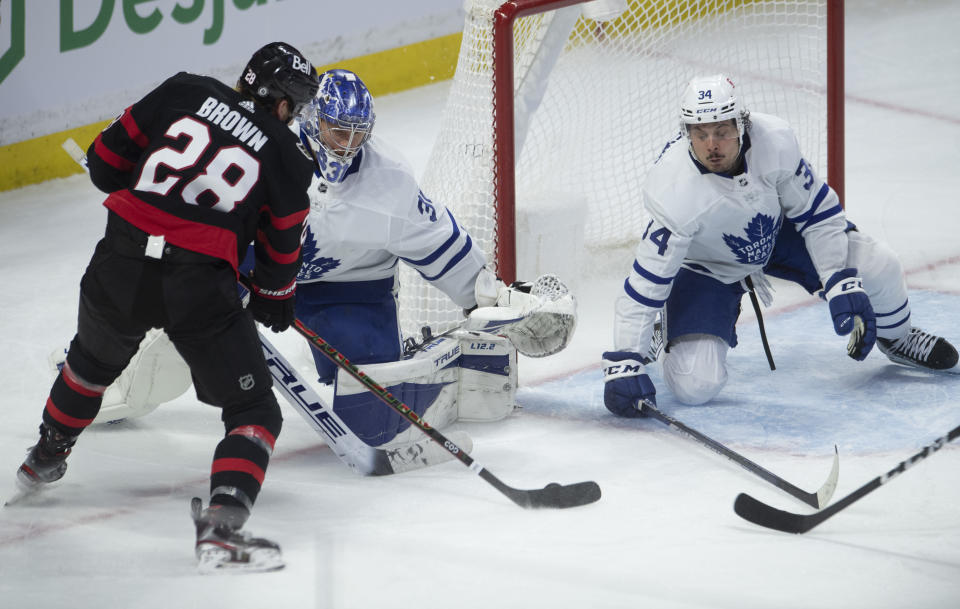 Ottawa Senators right wing Connor Brown prepares to shoot as Toronto Maple Leafs center Auston Matthews attempts to block the shot as goaltender Frederik Andersen is caught out of position during the second period of an NHL hockey game Wednesday, May 12, 2021, in Ottawa, Ontario. Brown scored on the play. (Adrian Wyld/The Canadian Press via AP)