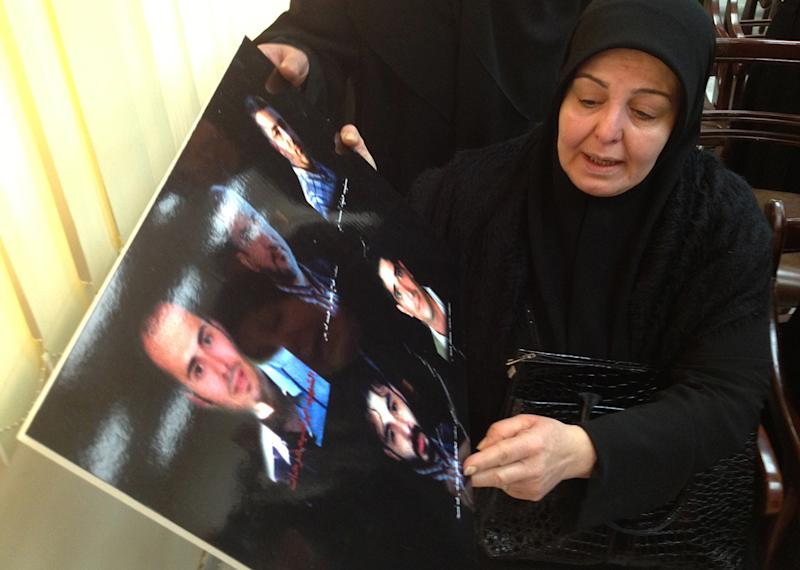 A Lebanese woman whose son was killed at the Iranian embassy attack in Beirut last November, holds a placard shows a portrait of her son and other victims, as she attends a press conference, in Beirut, Lebanon, Friday, Jan. 3, 2014. DNA tests confirmed that Majid al-Majid who is in Lebanese government custody is the alleged leader of an al-Qaida-linked group that has conducted attacks across the Middle East before shifting its focus to Syria's civil war, Lebanese authorities said Friday. Families of those killed in the embassy bombing demanded that al-Majid, who has not been charged in the attack, be tried in Lebanon and not be sent to his homeland. (AP Photo/Bassem Mroue)