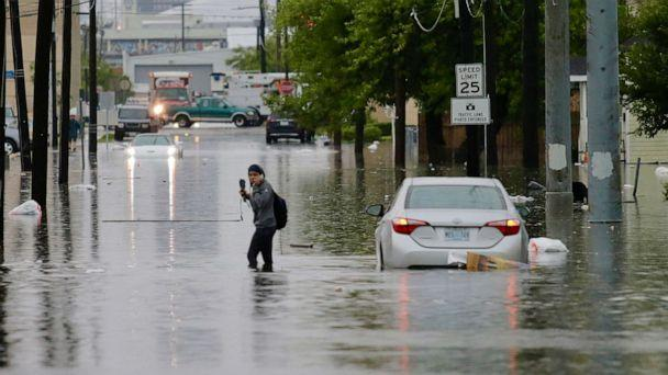 PHOTO: A person crosses a flooded road as heavy rain falls, July 10, 2019, in New Orleans. (Times-Picayune and New Orleans Advocate via AP)