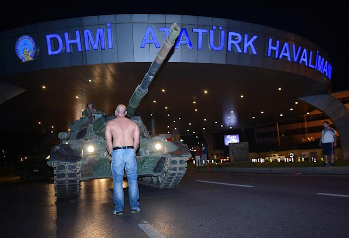 <p>JUL. 16, 2016 — A man stands in front of a tank in the entrance to Istanbul's Ataturk airport. Members of Turkey's armed forces said they had taken control of the country, but Turkish officials said the coup attempt had been repelled in a night of violence, according to state-run media. (Ismail Coskun/IHA via AP) </p>