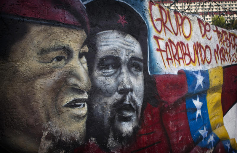 A mural of Venezuela's President Hugo Chavez, left, and Cuba's revolutionary hero Ernesto 'Che' Guevara covers a wall in Caracas, Venezuela, Wednesday Feb. 29, 2012.  Chavez underwent surgery Monday in Havana and aides said he was recovering well after a one-inch (two-centimeter) lesion was removed from the same part of the body where a larger, malignant tumor was taken out last summer. There has been no confirmation that the new tumor is cancerous. (AP Photo/Ariana Cubillos)