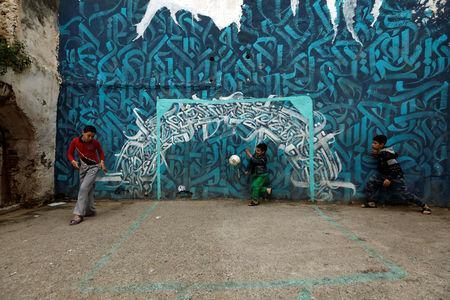 Abelraouf, 10, tries to save a goal in front of a goalpost painted on a wall during a soccer match in the old city of Algiers Al Casbah, Algeria May 5, 2018. REUTERS/Zohra Bensemra