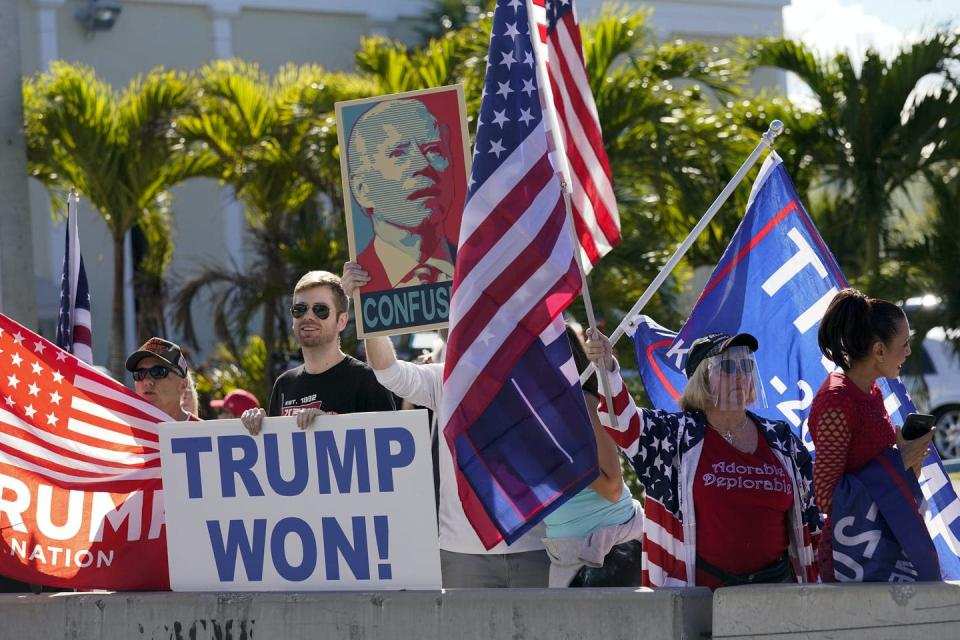 Trump supporters wave flags and hold a sign that say Trump Won