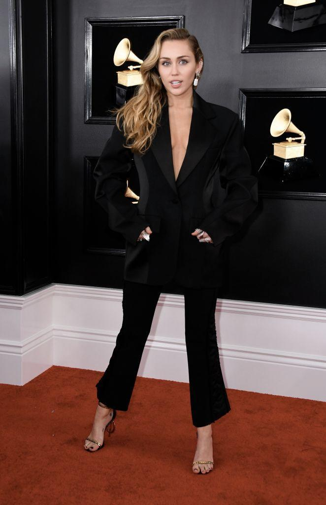 """<p>Did you really think Miley Cyrus would wear a plain old dress? The songstress, who always commands attention, rocked a blazer sans shirt underneath, along with personalized """"MC"""" shoes. </p>"""