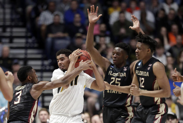 Missouri forward Jontay Porter (11) protects the ball from Florida State guard Trent Forrest (3), forward Mfiondu Kabengele (25) and center Ike Obiagu (12) in the first half of a first-round game of the NCAA college basketball tournament in Nashville, Tenn., Friday, March 16, 2018. (AP Photo/Mark Humphrey)