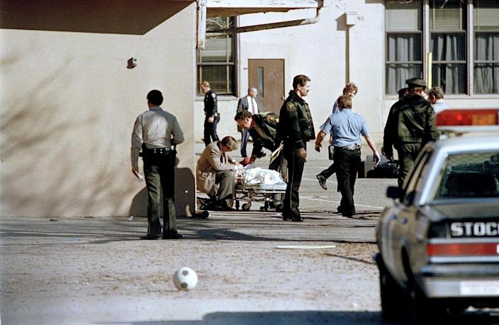 Police around a covered body lying on a gurney in a schoolyard