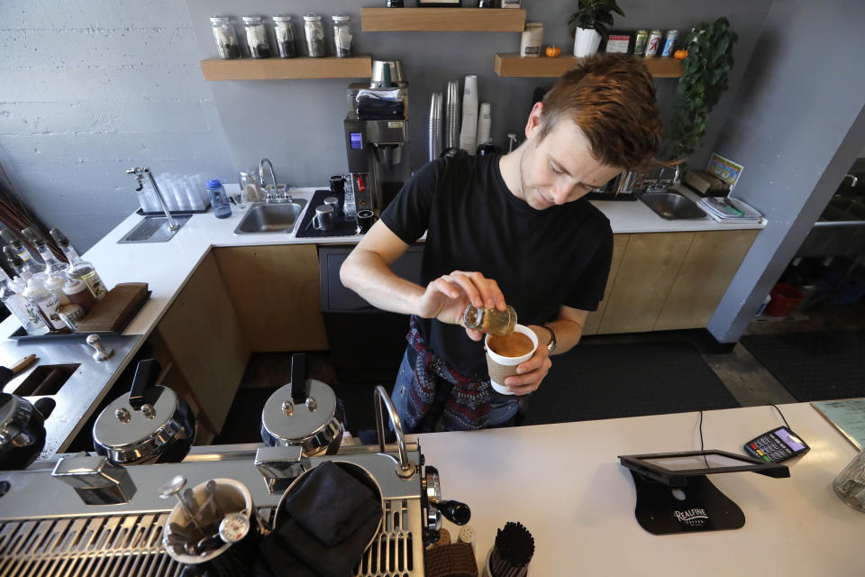 In this photo taken Monday, Nov. 4, 2019, barista Porter Hahn makes an iced coffee drink for a customer in a coffee shop in Seattle. (AP Photo/Elaine Thompson)
