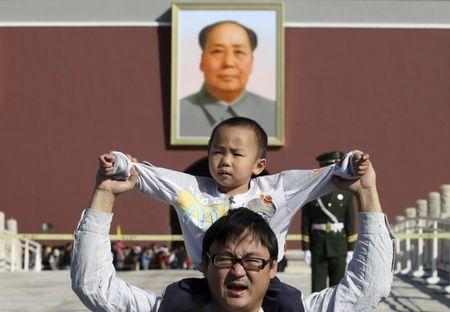 A boy sits on his father's shoulders as they pose for a photograph in front of the giant portrait of late Chinese chairman Mao Zedong on the Tiananmen Gate, in Beijing, China, October 2, 2011. REUTERS/Stringer