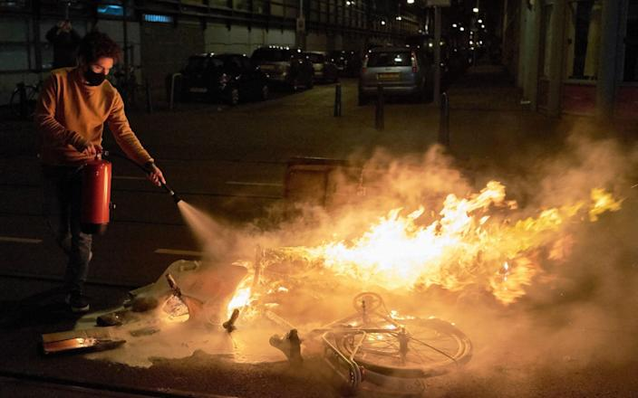 A resident extinguishes a burning bin and a bycicle as groups of local youth gather on the streets of Schilderswijk for a second day