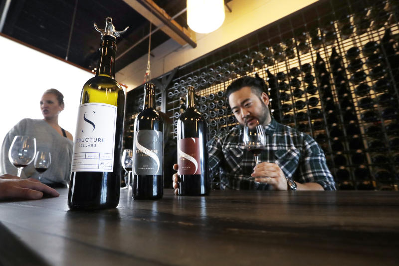 In this photo taken Thursday, Nov. 21, 2019, Mike Roh sniffs wine before tasting it at Structure Cellars wine tasting room in Seattle, Wash. From less than 20 wineries in 1981, the Washington wine industry has grown to more than 1,000 this year. The state is the second-largest producer of premium wines in the U.S., trailing only California. (AP Photo/Elaine Thompson)