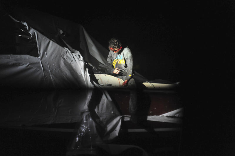 In this Friday, April 19, 2013 photo provided by the Massachusetts State Police, Boston Marathon bombing suspect Dzhokhar Tsarnaev leans over in a boat at the time of his capture by law enforcement authorities in Watertown, Mass. Photos of the Boston Marathon bombing suspect's surrender have been posted on the Boston Magazine website. The additional images, made public Tuesday, Aug. 27, 2013, were among those released to the magazine last month by a state police photographer. (AP Photo/Massachusetts State Police, Sean Murphy)