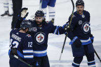 Winnipeg Jets' Jansen Harkins (12), Nate Thompson (11) and Dylan DeMelo (2) celebrate Harkins' goal against the Toronto Maple Leafs during the third period of an NHL hockey game Friday, May 14, 2021, in Winnipeg, Manitoba. (John Woods/The Canadian Press via AP)
