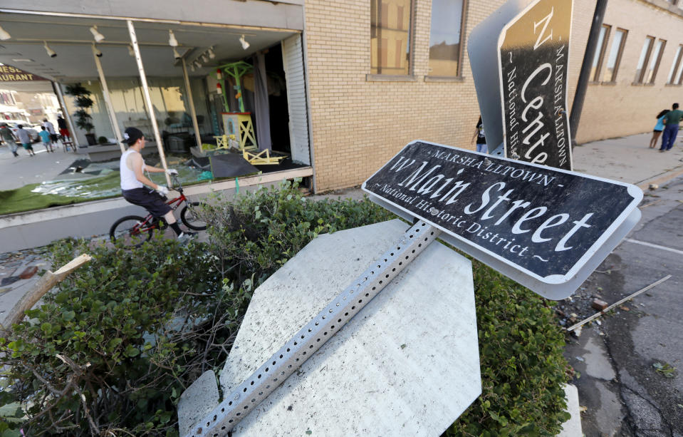 <p>A local resident rides his bike past a toppled street sign on Main Street, Thursday, July 19, 2018, in Marshalltown, Iowa. Several buildings were damaged by a tornado in the main business district in town including the historic courthouse. (Photo: Charlie Neibergall/AP) </p>