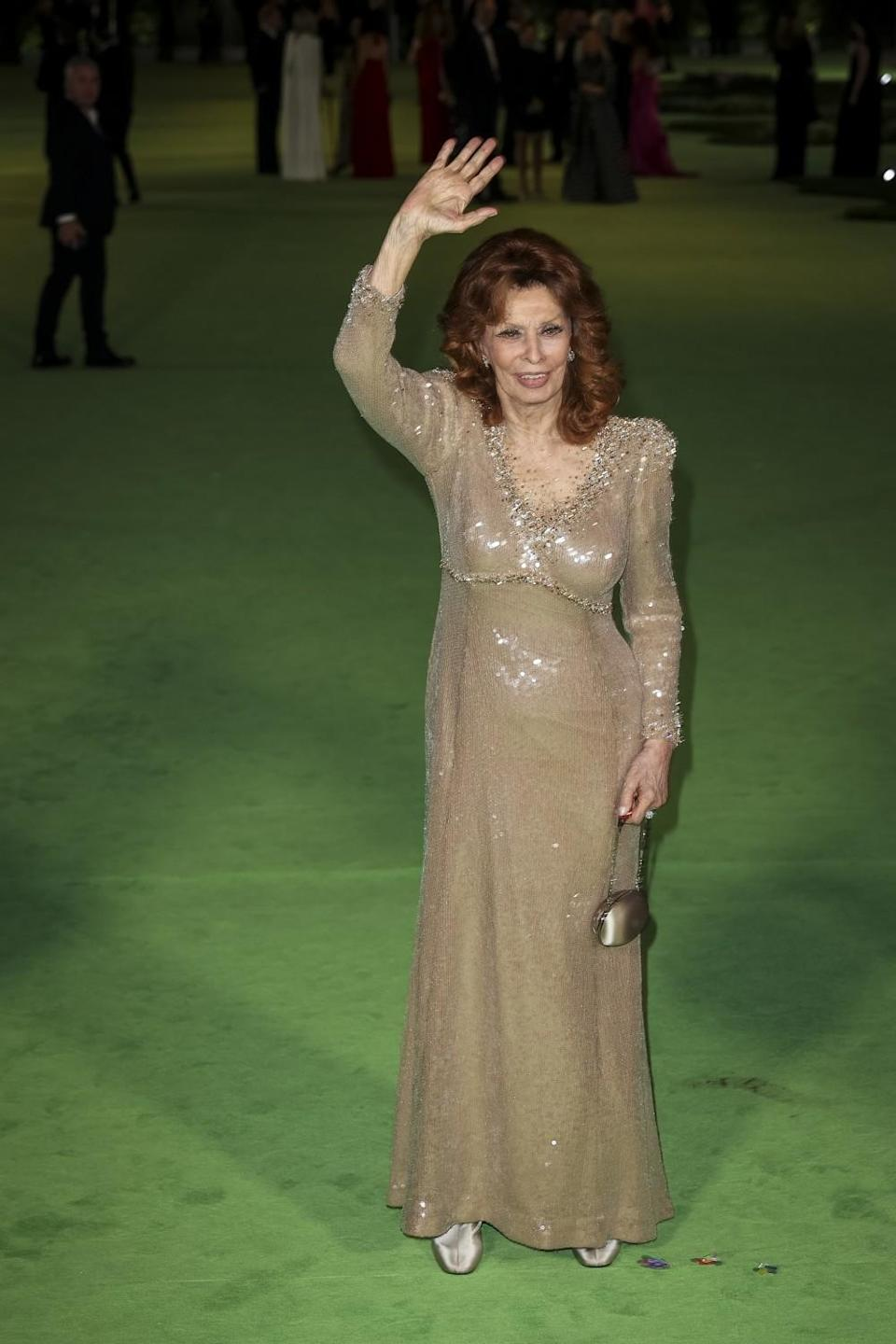A woman in a gold dress waving on a green carpet