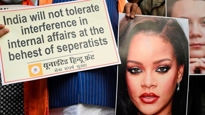 Activists of United Hindu Front (UHF) hold a placard and pictures of Swedish climate activist Greta Thunberg and Barbadian singer Rihanna during a demonstration in New Delhi on February 4, 2021, after they made comments on social media about ongoing mass farmers' protests in India.