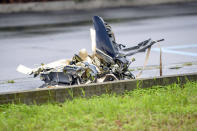 Metallic pieces lie on the site of a plane crash, in San Donato Milanese suburb of Milan, Italy, Sunday, Oct. 3, 2021. According to media reports, a small plane carrying five passengers and the pilot crashed into an apparently vacant office building in a Milan suburb. Their fates were not immediately known. (Claudio Furlan/LaPresse via AP)
