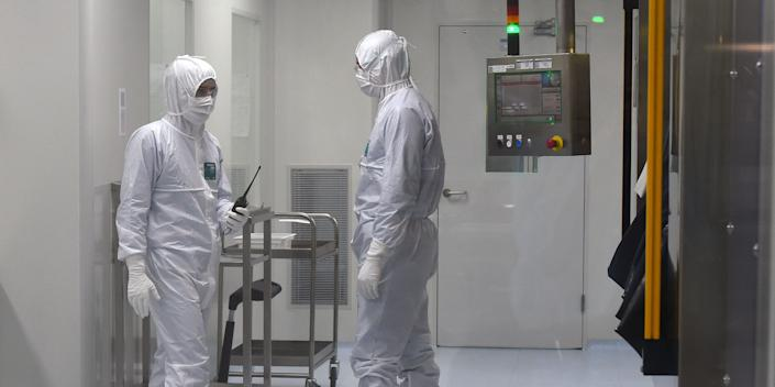 Employees wearing protective equipment work at the production line of Russia's biotech company BIOCAD, which is developing its own vaccine against the new coronavirus and working on another one in cooperation with the country's virus research centre in Siberia, Vektor, in Strelna on May 20, 2020. (Photo by OLGA MALTSEVA / AFP) (Photo by OLGA MALTSEVA/AFP via Getty Images)