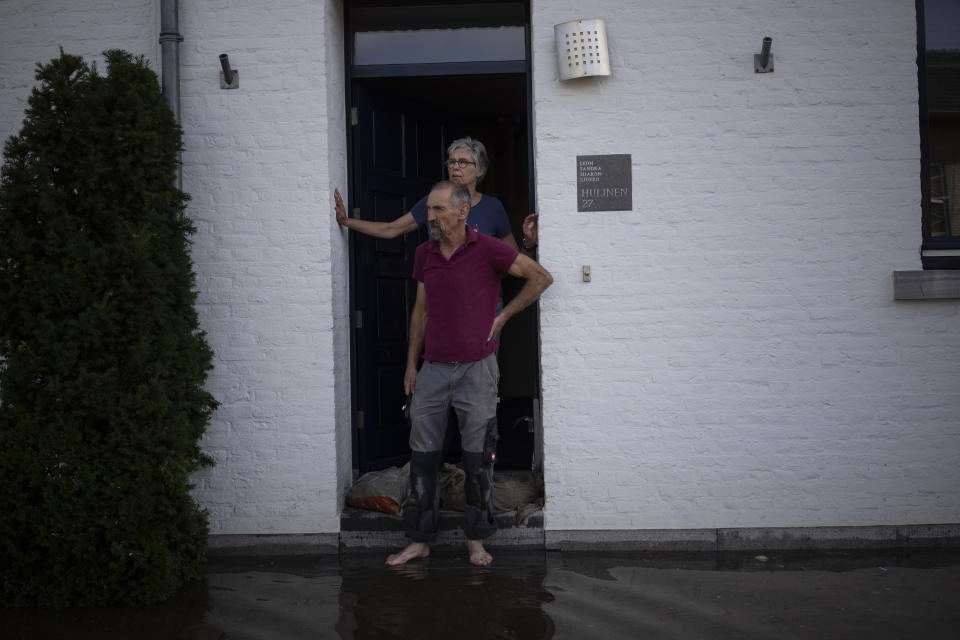 A coupe stands outside their home, in the town of Brommelen, Netherlands, Saturday, July 17, 2021. In the southern Dutch province of Limburg, which also has been hit hard by flooding, troops piled sandbags to strengthen a 1.1-kilometer (0.7 mile) stretch of dike along the Maas River, and police helped evacuate low-lying neighborhoods. (AP Photo/Bram Janssen)