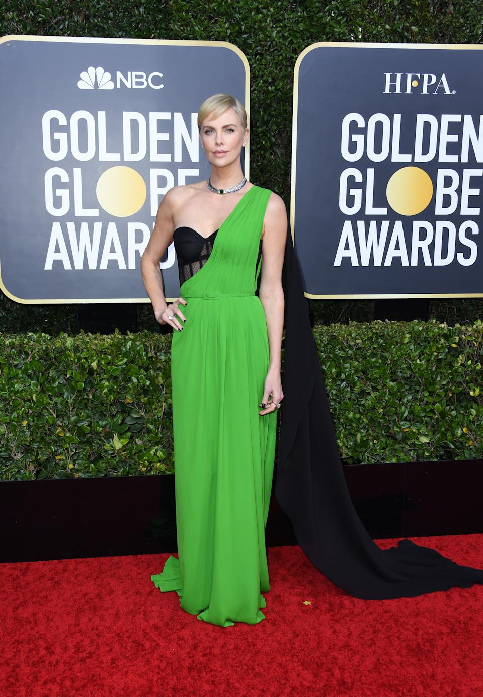 """The """"Bombshell"""" star opted for a bold green and black gown with flowing cape detail by Dior. (Photo by Jon Kopaloff/Getty Images)"""