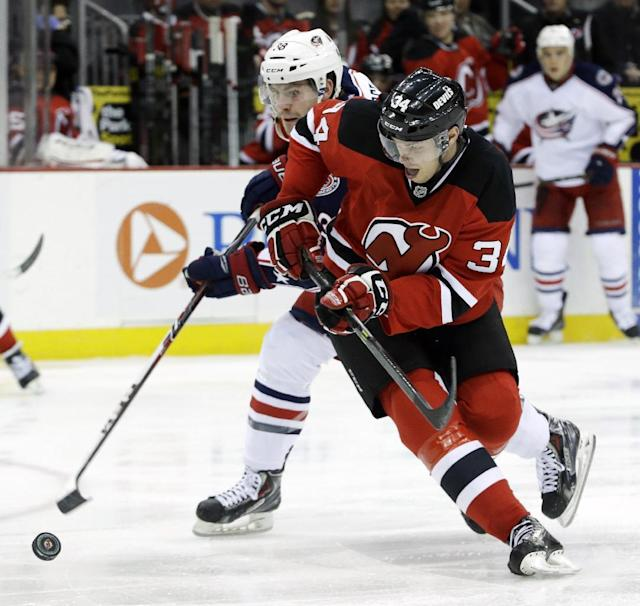 New Jersey Devils' Jon Merrill (34) and Columbus Blue Jackets' Boone Jenner compete for the puck during the first period of an NHL hockey game, Friday, Dec. 27, 2013, in Newark, N.J. (AP Photo/Julio Cortez)