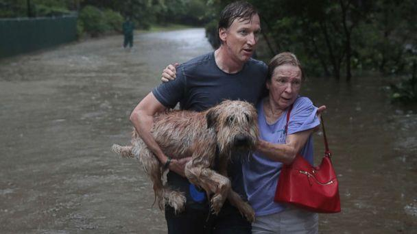 PHOTO: Andrew White (L) helps a neighbor down a street after rescuing her from her home in his boat in the upscale River Oaks neighborhood after it was inundated with flooding from Hurricane Harvey, Aug. 27, 2017, in Houston. (Scott Olson/Getty Images)