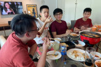 Malaysian students, from left, Felix Mong, Jason Ong, Ter Leong Kern and Siew Ee Sung eat bak kwa, a Chinese meat product similar to jerky, during a Lunar New Year hot pot lunch hosted by a Malaysian couple at their rented apartment in Singapore, Saturday, Feb. 13, 2021. With Malaysian workers and students stranded in the city state over the Lunar New Year due to coronavirus travel restrictions, the Malaysian Association in Singapore has called on Malaysians to treat students to a meal. (AP Photo/Annabelle Liang)
