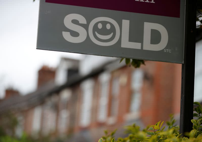 An estate agent's board stands outside a housing development in Manchester