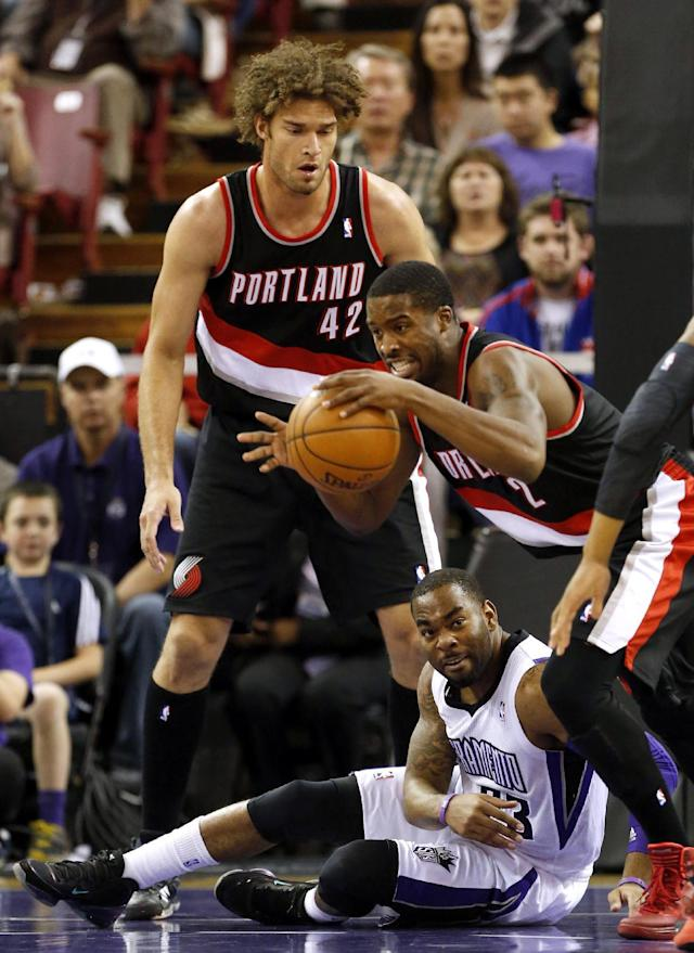 Portland Trail Blazers guard Wesley Matthews, right, comes up with the loose ball over Sacramento Kings guard Marcus Thornton, center, as Trail Blazers center Robin Lopez stands by during the first quarter of an NBA basketball game in Sacramento, Calif., Saturday, Nov. 9, 2013. (AP Photo/Rich Pedroncelli)