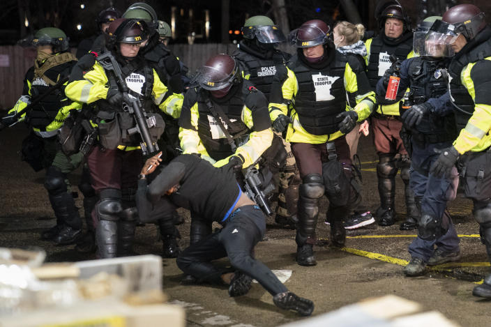 A demonstrator is arrested by police for violating curfew and an order to disperse during a protest against the police shooting of Daunte Wright, late Monday, April 12, 2021, in Brooklyn Center, Minn. (AP Photo/John Minchillo)
