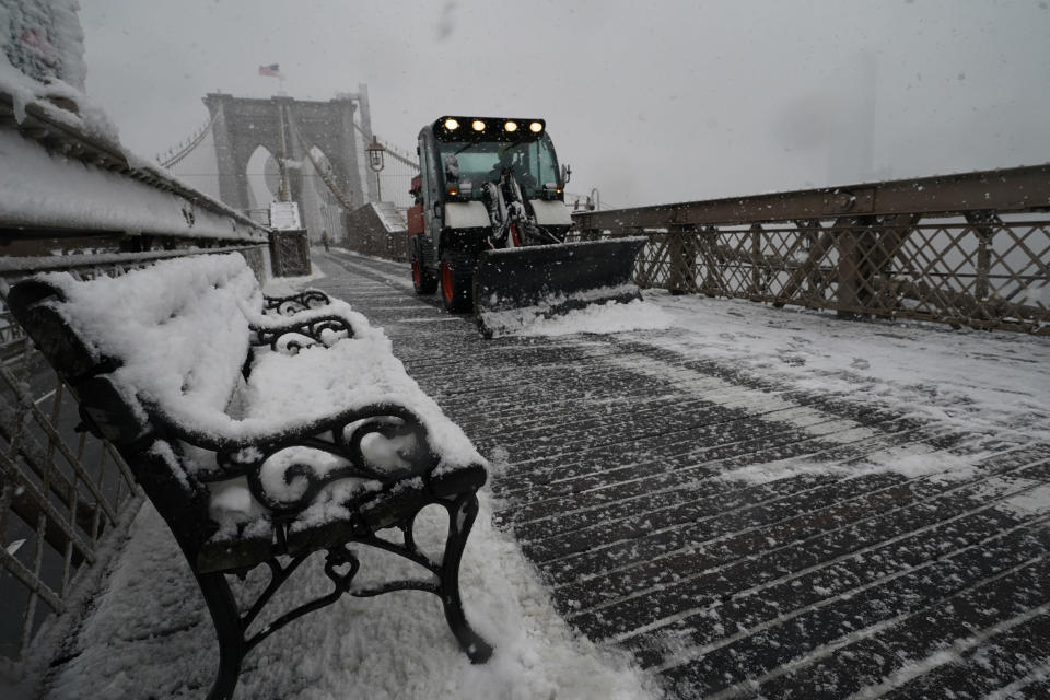 A snowplow makes it's way across the pedestrian walkway of the Brooklyn Bridge during a snowstorm, Sunday, Feb. 7, 2021, in New York. It was the second major snowstorm in less than week to hit the area. (AP Photo/Kathy Willens)