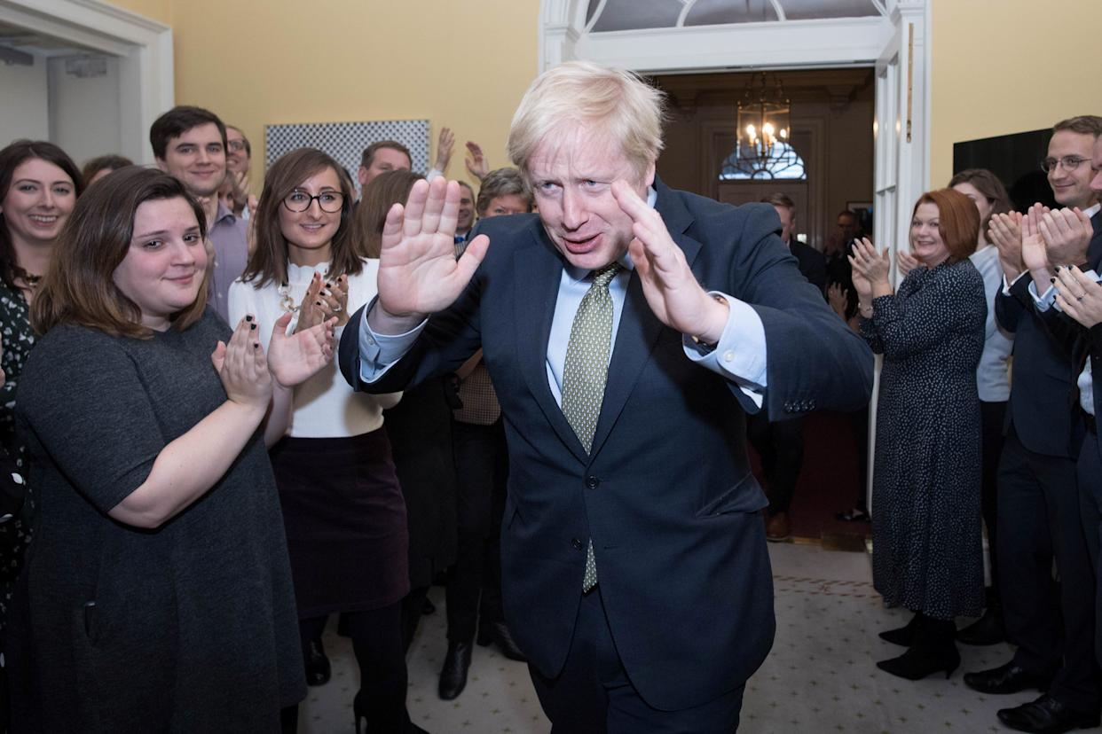 Britain's Prime Minister Boris Johnson reacts as he is greeted by staff, arriving back at Downing Street, after meeting Queen Elizabeth and accepting her invitation to form a new government, in London, Britain December 13, 2019. Stefan Rousseau/Pool via REUTERS