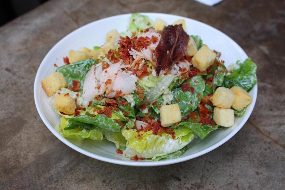 The only cold dish on the cheese wheel menu, the Caesar salad ($19) is mixed with a D10 classic dressing before being topped with croutons, smoked chicken and bacon bits. (Photo: Yahoo Singapore)