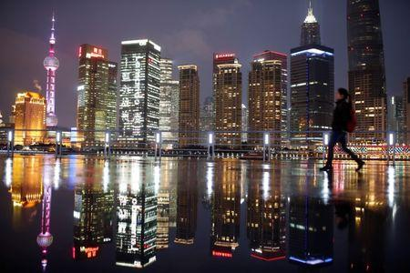 FILE PHOTO: Woman walks at the Bund in front of the financial district of Pudong in Shanghai