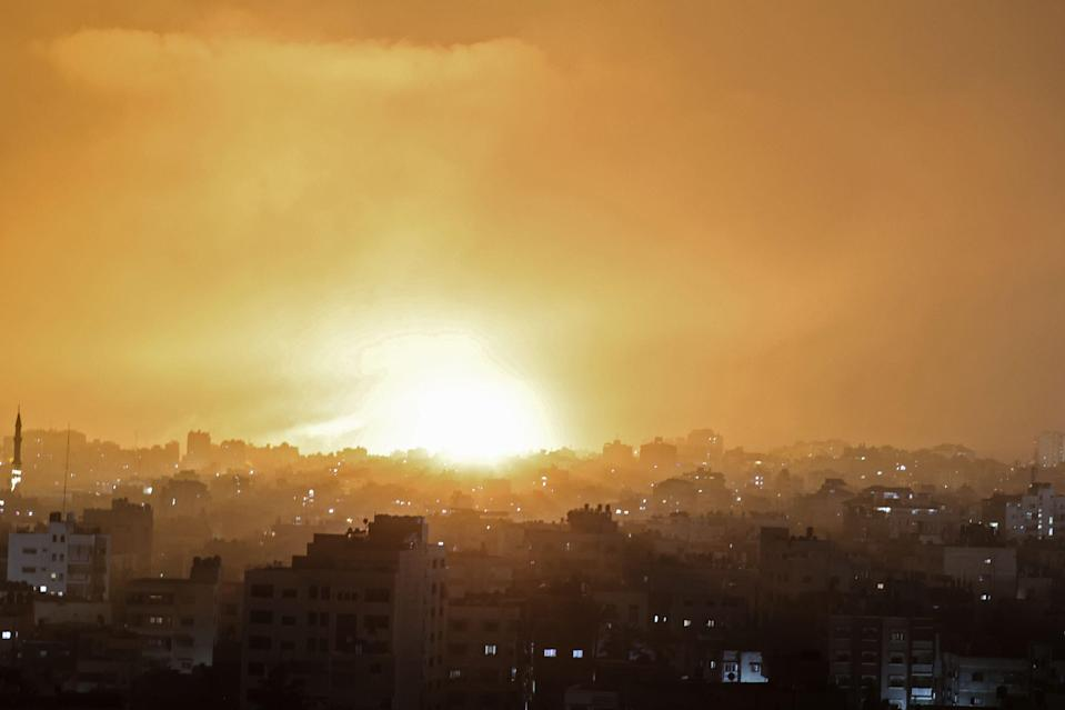 <p>Red flames lit up the skies as the  blasts from the outskirts of Gaza City jolted people awake.</p> (AFP via Getty Images)