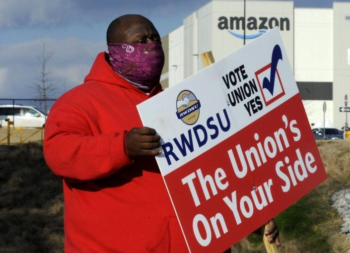 A man in a red coat holding a pro-union sign stands outside an Amazon facility in Bessemer, Alabama