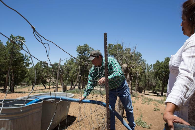 Jacob Antone fill his water trough on July 7, 2019, in Whitegrass, Arizona. The Antone's haul water for their horses every three days. Looking on is Grace Antone.