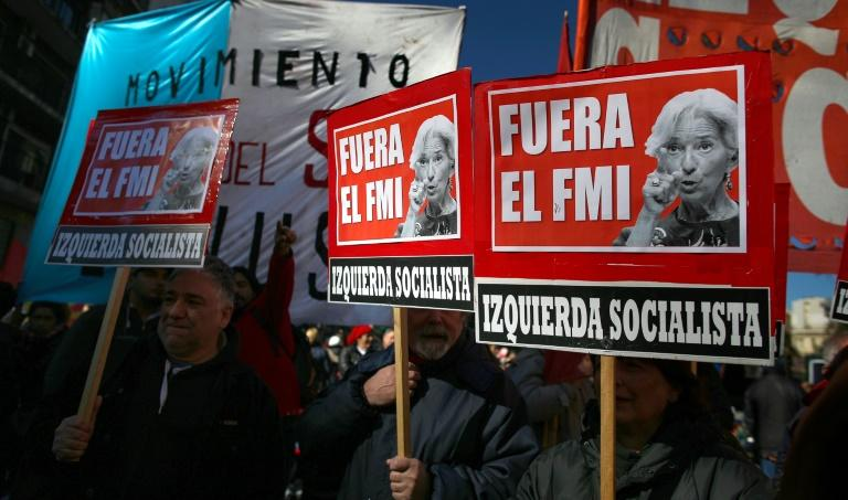 "Demonstrators in Buenos Aires hold placards reading ""IMF Out"" during a protest against Argentina's latest agreement with the International Monetary Fund"