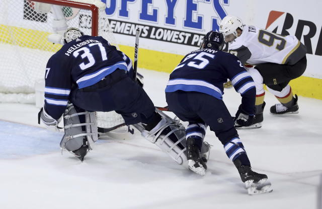 Las Vegas Golden Knights' Tomas Tatar (90) scores on Winnipeg Jets goaltender Connor Hellebuyck (37) with Paul Stastny (25) in front of the net during first period game 2 NHL Western Conference Finals hockey action in Winnipeg, Manitoba, Monday, May 14, 2018. (Trevor Hagan/The Canadian Press via AP)