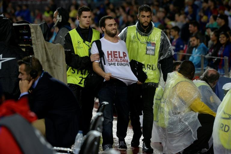 A man sporting a t-shirt demanding help for Catalonia is let out of the stadium by security personnel during the UEFA Champions League match between Barcelona and Olympiacos at the Camp Nou stadium in Barcelona